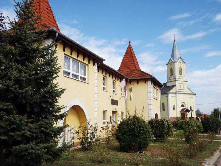 Nyírlugos - Az óvoda és teleház épülete a katolikus templom mellett áll