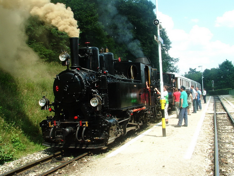 Two steam-engines pull the long train on the hard upward slope