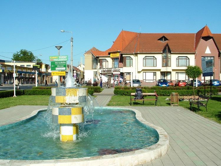 The building of Gömör Áruház stands beside a small park