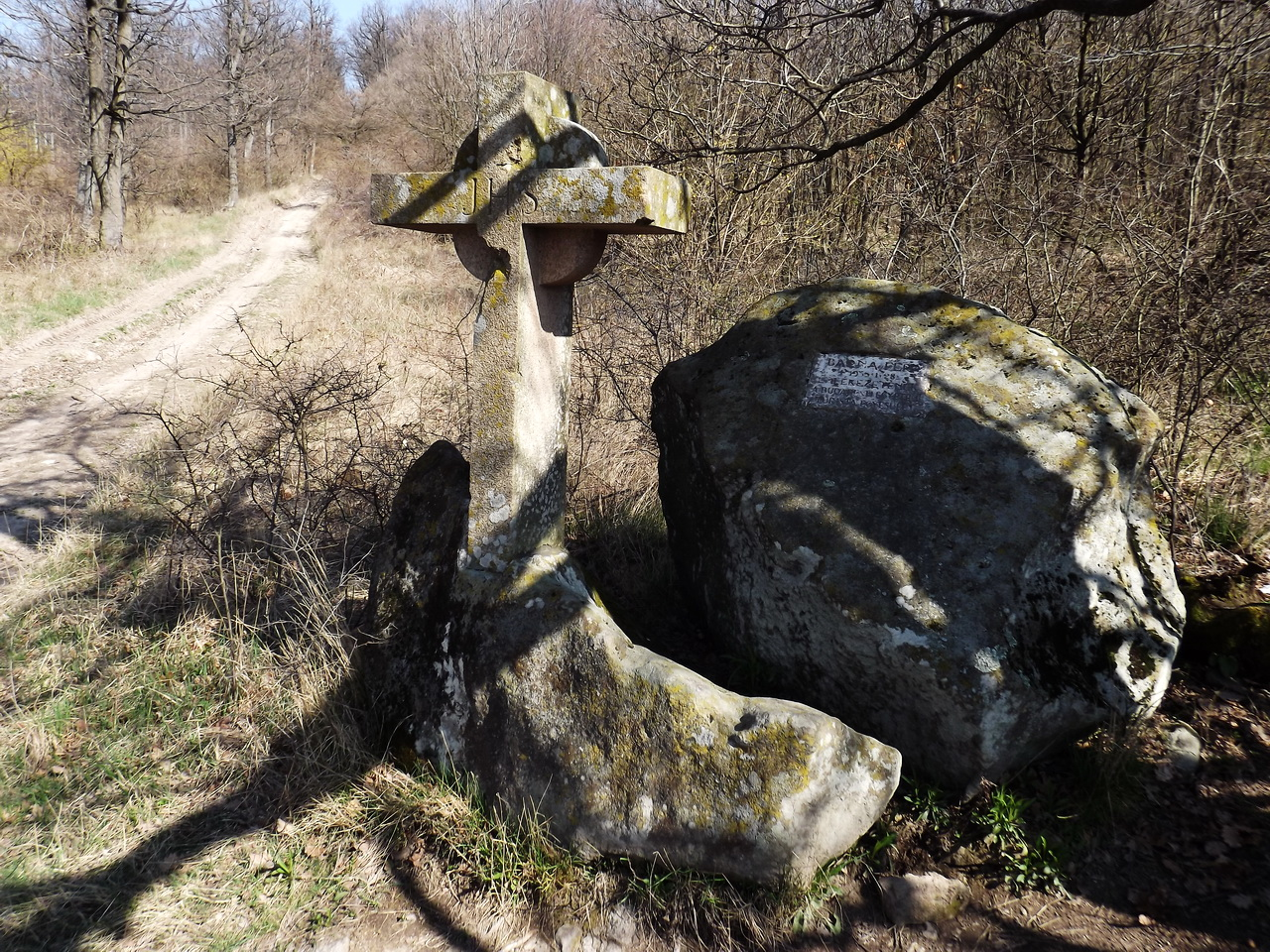 The Barna Ferenc Stone Cross stands beside the dirt road