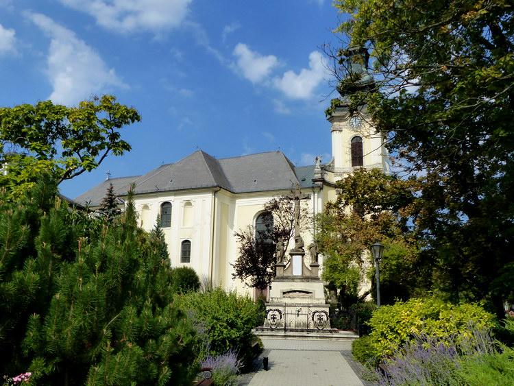 A római katolikus plébániatemplom az emlékműtől fényképezve