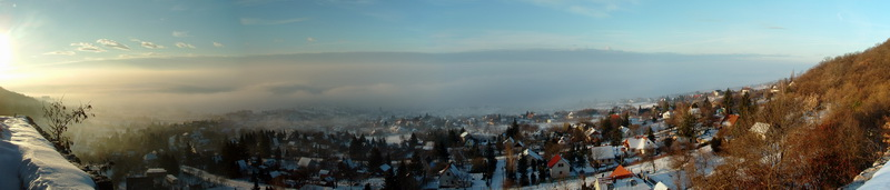 Winter panoramic view from Castle of Csókakő to the village and the foggy environs